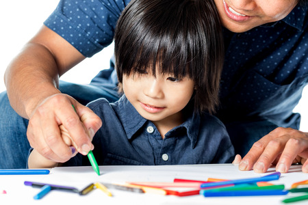 pre schooler: Close up portrait of Asian dad helping little boy with drawings.Isolated on white background. Stock Photo
