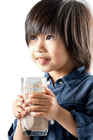 milk mustache: Close up portrait of cute asian boy holding glass with chocolate milk.Isolated on white background.