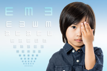 testing vision: Close up conceptual portrait of little Asian child testing vision with chart.Boy closing one eye with hand and symbol test chart in background.