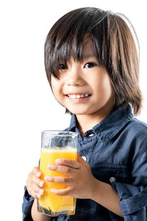 face shot: Close up face shot of Asian kid holding glass with orange juice.Isolated on white background. Stock Photo
