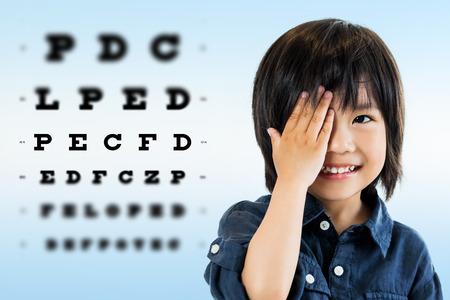 Gros plan, portrait d'un petit garçon asiatique mignon faisant des tests d'oeil. Cochez un oeil avec la main contre le tableau de test alphabétique hors de portée en arrière-plan. Banque d'images