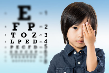 myopia: Close up portrait of handsome little asian boy testing eyesight.Kid closing one eye with hand against alphabetical out of focus eye test chart in background. Stock Photo