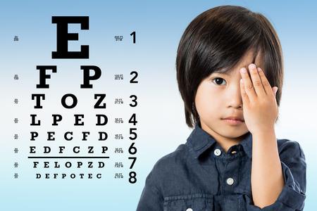 視力を見直しアジア少年の肖像画を間近します。子供の手とバック グラウンドでアルファベット順目のテストのグラフで 1 つ目を閉じるします。