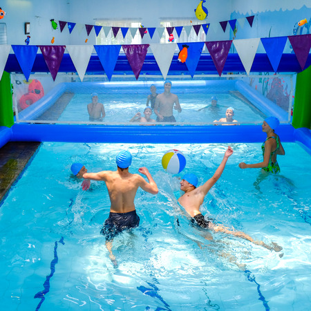 opponents: Action shot of kids playing indoor water volleyball game.