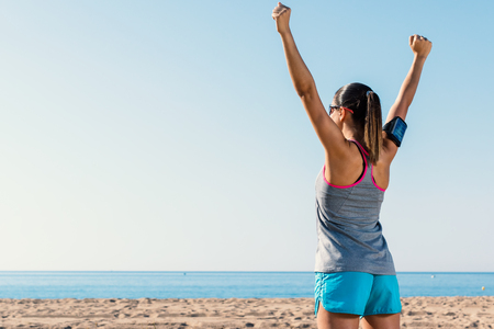 medium shot: Medium shot of young female runner raising arms at sea. Rear view of girl with victorious attitude. Stock Photo
