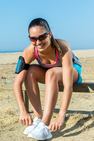 beach front: Close up portrait of attractive female runner getting ready to run along beach front.