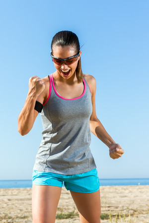 Close up portrait of muscular girl in sportswear pulling a fist. Young woman with winning attitude at beach.