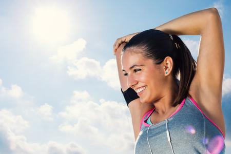 De cerca la cara del tiro de corredor joven atractiva que consigue listo para run.Woman mañana con sonrisa encantadora que estira los brazos y el cuello contra el cielo nublado. Foto de archivo