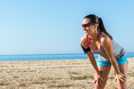 beach front: Close up of attractive young girl jogger taking a rest.Woman standing with hands on knees at beach front.