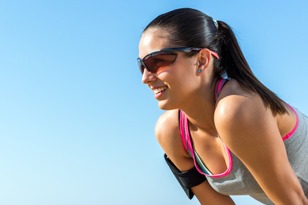 eye wear: Close up portrait of young athlete with sportive eye wear and smart phone activity armband against blue sky.
