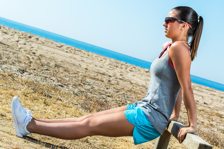warming up: Full length portrait of attractive muscular female runner warming up at sea side.