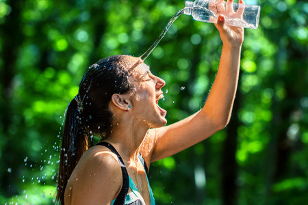 face shot: Close up face shot of female runner pouring water on face after workout. Cold water from bottle splashing on girls face against green background.