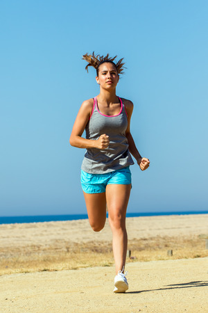 towards: Full length front view action shot of attractive young girl athlete running towards camera.