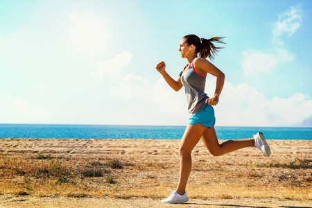 beach front: Full length in motion shot of attractive young woman jogging along beach front on sunny morning. Stock Photo