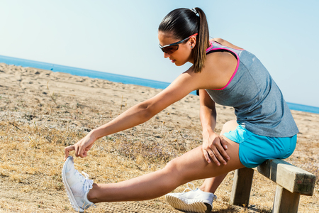 loosen up: Full length portrait of muscular young female runner stretching hamstrings at beach front.
