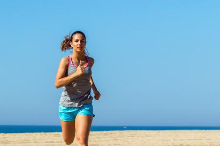 medium shot: Medium shot of young woman jogging outdoors against blue sky.