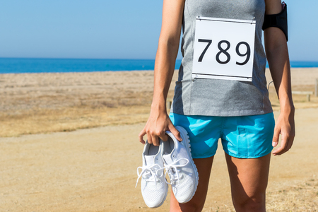 dorsal: Close up of female athlete with dorsal start number holding running shoes. Body part of girl outdoors at beachfront.