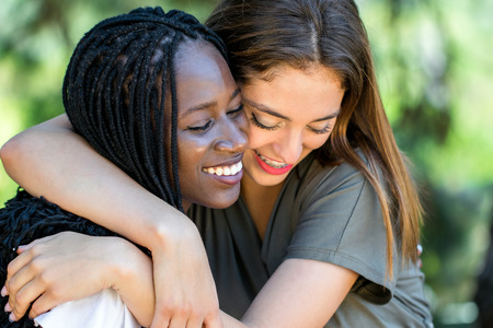 symbolism: Close up face shot portrait of two multiracial friends showing affection outdoors. Stock Photo