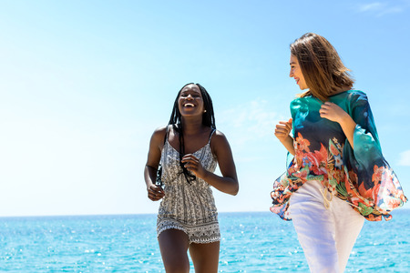 Close up action portrait of attractive african woman and caucasian girlfriend laughing and running together on beach.