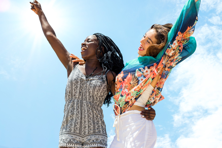 action shot: Close up action shot of young african woman jumping together with caucasian girlfriend against blue sky.