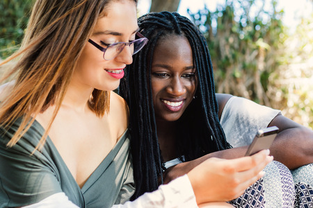 Close up portrait of two teen girls looking at smart phone together. Black and white girls socializing on digital device.