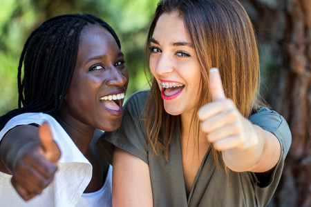 Close up face shot of cute young multiracial girlfriends couple doing thumbs up outdoors.