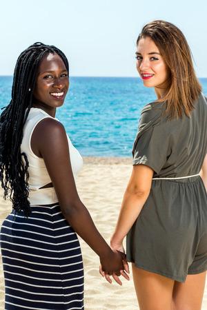 Cerca retrato de dos muchachas adolescentes que llevan a cabo adolescente hands.African coloca en la playa con su amigo caucásico.