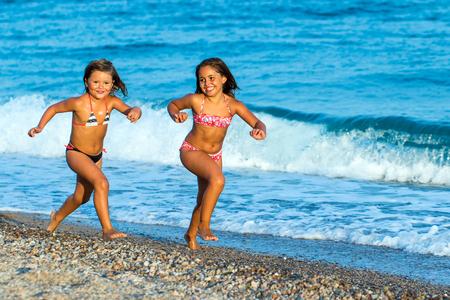 traje de baño: Cerca retrato acción de dos chicas jóvenes que se ejecutan junto en la playa de guijarros. Foto de archivo
