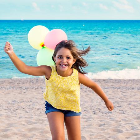 girl action: Action portrait of cute little girl running on beach with balloons. Stock Photo