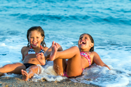 Close up portrait of two little girls having fun together in waves. Stock Photo