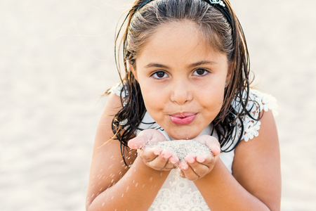 pre teen girls: Close up Face shot of little girl blowing sea sand.