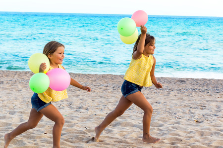 Action portrait of little girls chasing on beach with color balloons. photo