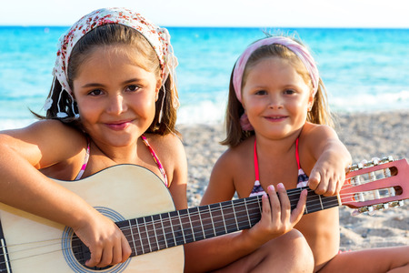 Close up portrait of two little girls having fun with guitar on beach. photo