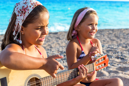 Close up portrait two little girls wearing headbands singing together on beach. One girl playing guitar and other in background clapping hands. photo