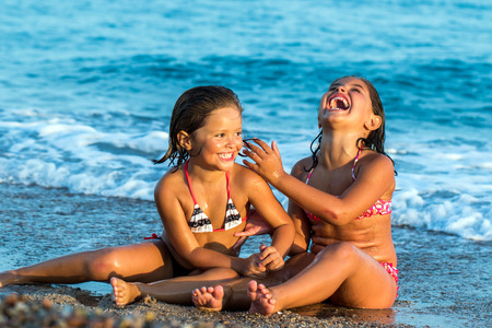 Close up portrait of little girls laughing together.Two kids sitting on sand with waves in background. photo