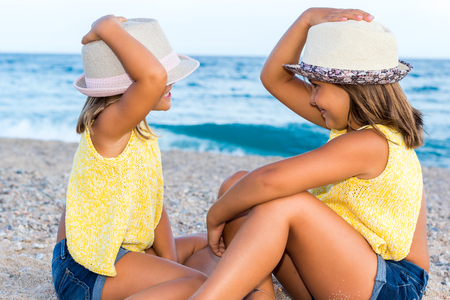 Close up portrait of  little girls wearing hats sitting on beach.Side view of kids looking at each other. photo