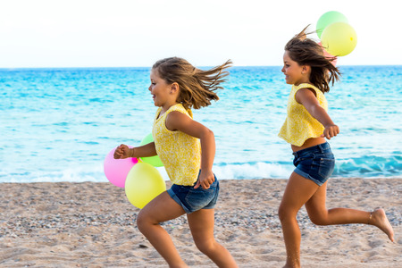 Close up action portrait of two little sisters running together on beach with color balloons. photo