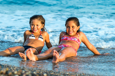 Close up portrait of young girls enjoying summer holidays together on beach. photo