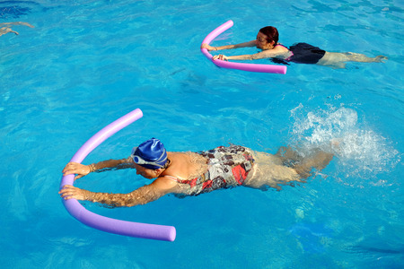Top view of two senior women doing swimming exercise with soft foam noodles in outdoor swimming pool. Stockfoto