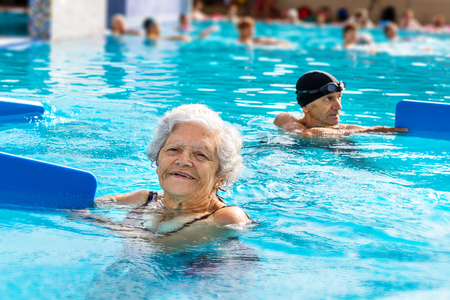 Close up portrait of elderly woman doing rehabilitation exercise in outdoor swimming pool.