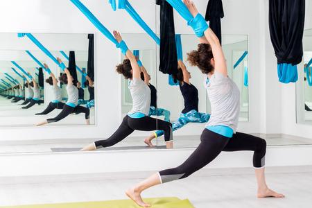 Full length portrait of two women practicing aerial yoga in studio.