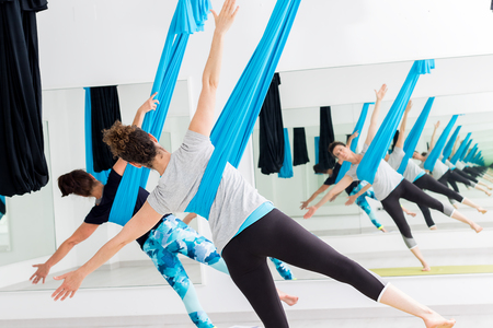 Close up of women exercising bodies at aerial yoga session in gym.