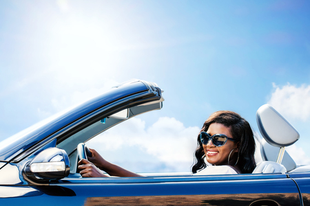 Close up portrait of attractive afro american woman driving blue convertible.