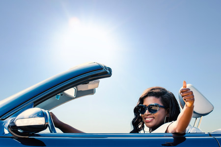 new car: Close up portrait of young afro american girl sitting in convertible doing thumbs up.