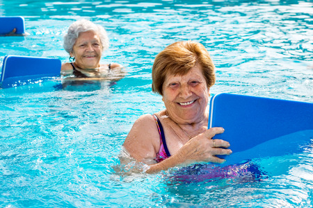 70s: Close up portrait of two senior women doing aqua gym with kicking boards in outdoor swimming pool.