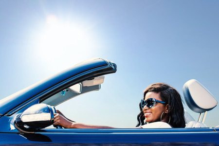 black car: Close up portrait of young african girl taking blue convertible for a test drive.