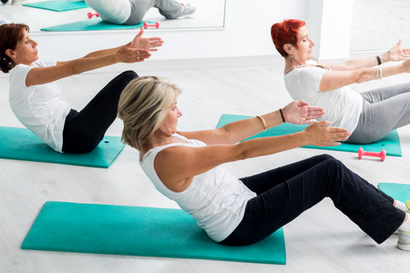 aged: Group of middle aged women doing abdominal exercise in gym.