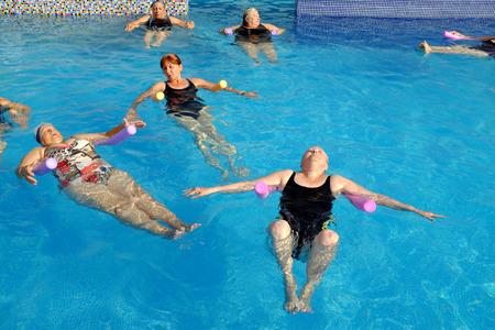 breathing exercise: Group of senior women doing breathing exercise in outdoor swimming pool. Stock Photo