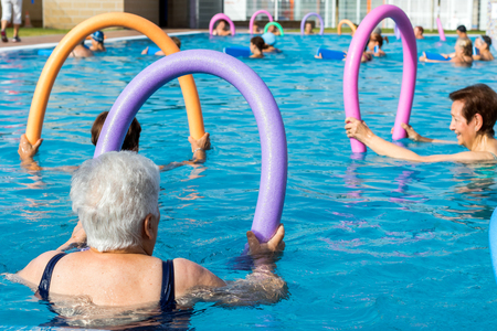 Group of senior women doing rehabilitation exercise with soft foam noodles in outdoor swimming pool.