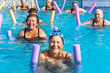 tercera edad: Grupo de mujeres de mayor activa que hace gimnasia acuática en la piscina exterior. Foto de archivo
